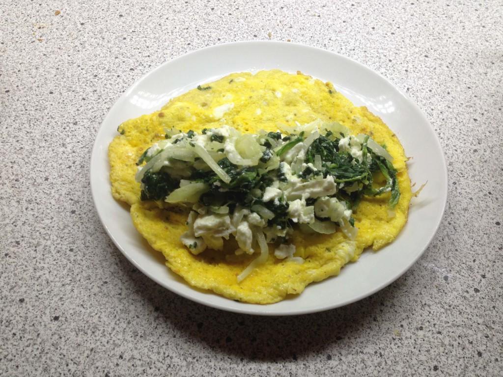 Die Hälfte der Füllung auf dem Omelette verteilen. (vh)