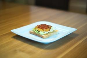 Die Patties auf Toast, Salat und mit Tomatensauce anrichten (vh)