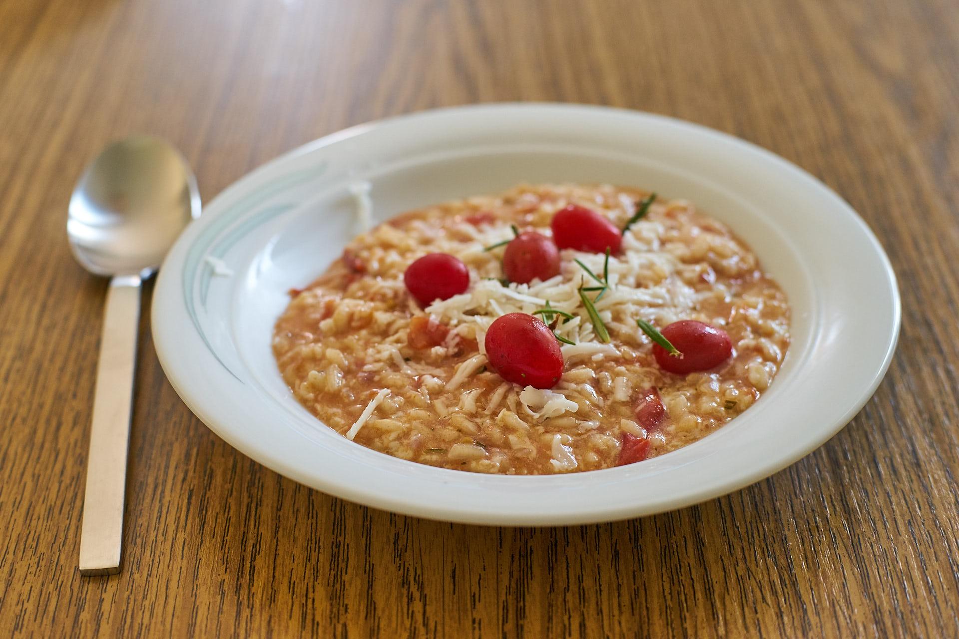 Eine Portion Tomaten-Ziegenkäse-Risotto mit Rosmarin.