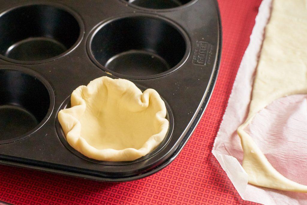 Muffinbleche mit einem Teig auslegen.