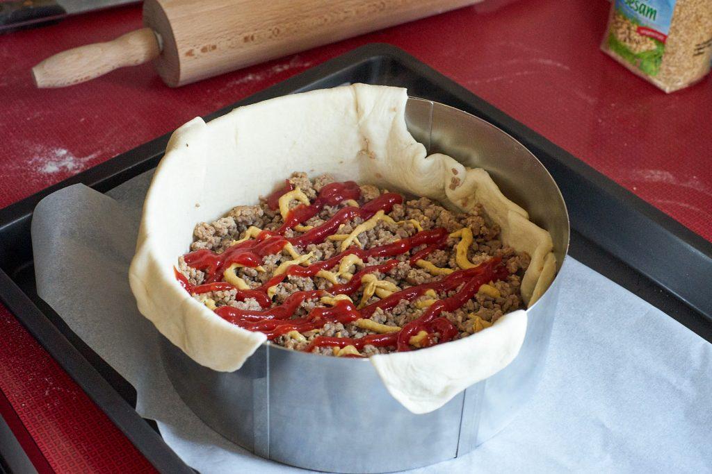 Der Kuchen wird mit Fleisch und anderen Zutaten gefüllt.