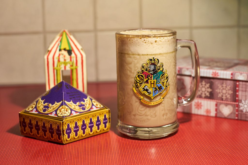 Ein Glas Butterbier und Süßigkeiten aus Hogwarts.