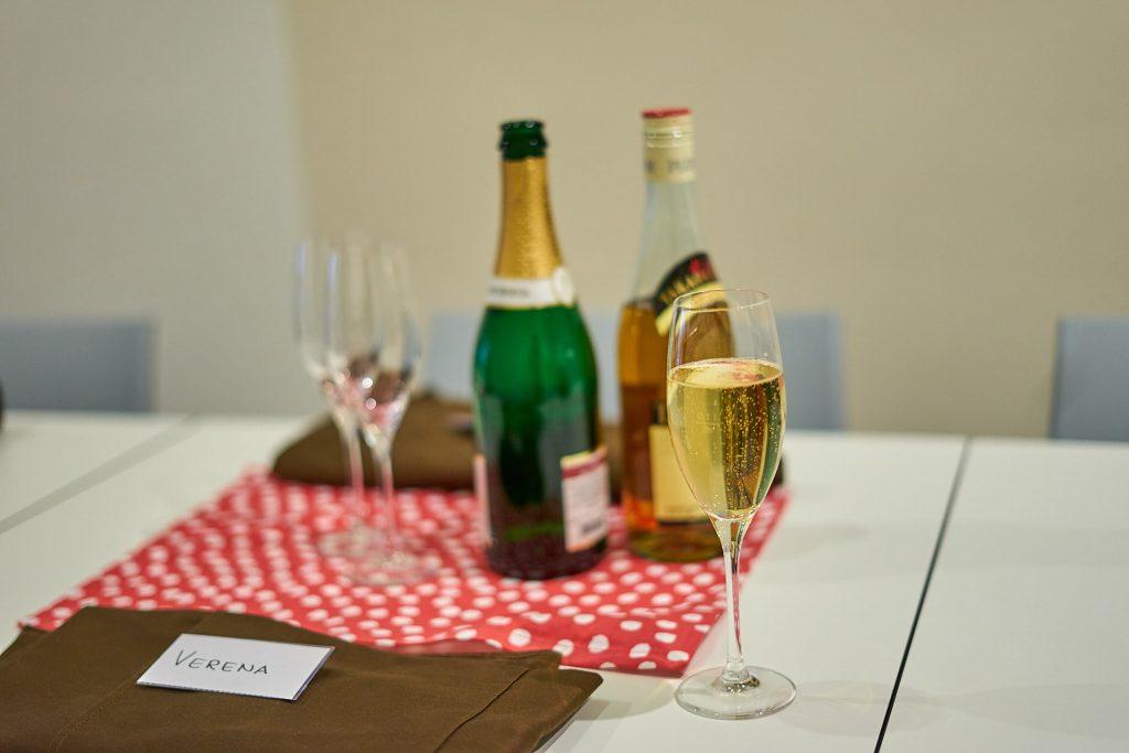 Ein Sektglas - im Hintergrund eine Flasche Sekt und eine Flasche Pflaumenwein. Sushi-Kurs Linz.