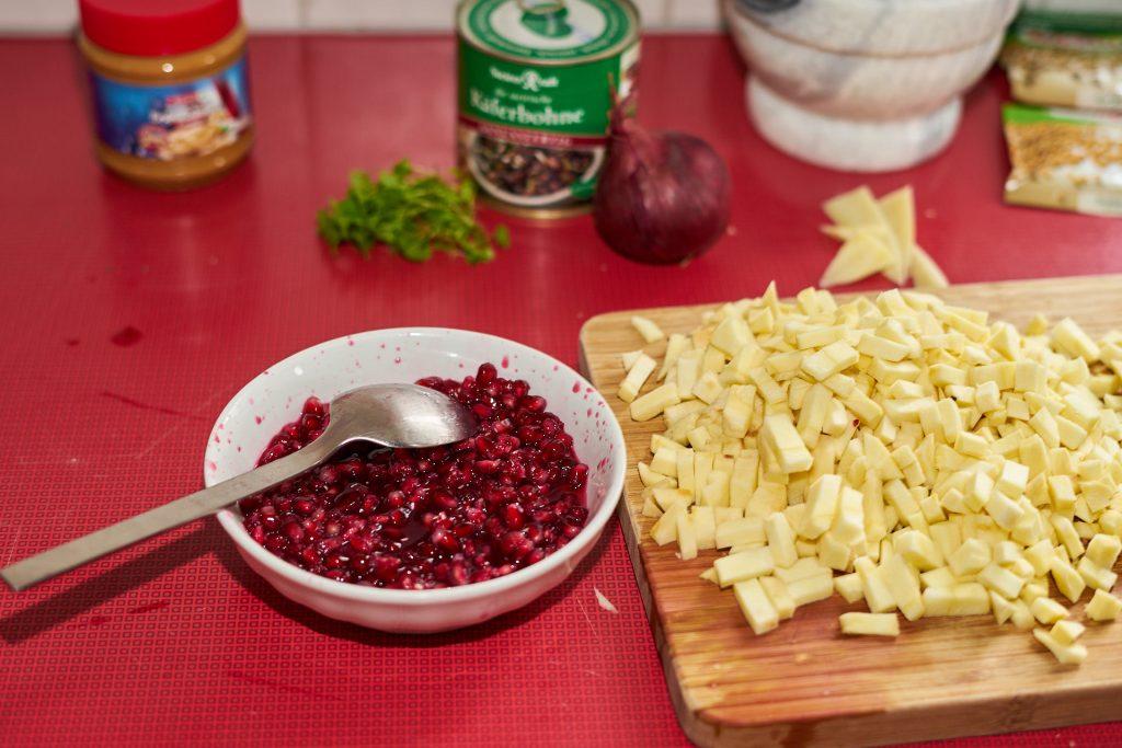 Geschnittene Pastinake und Granatapfelkerne.