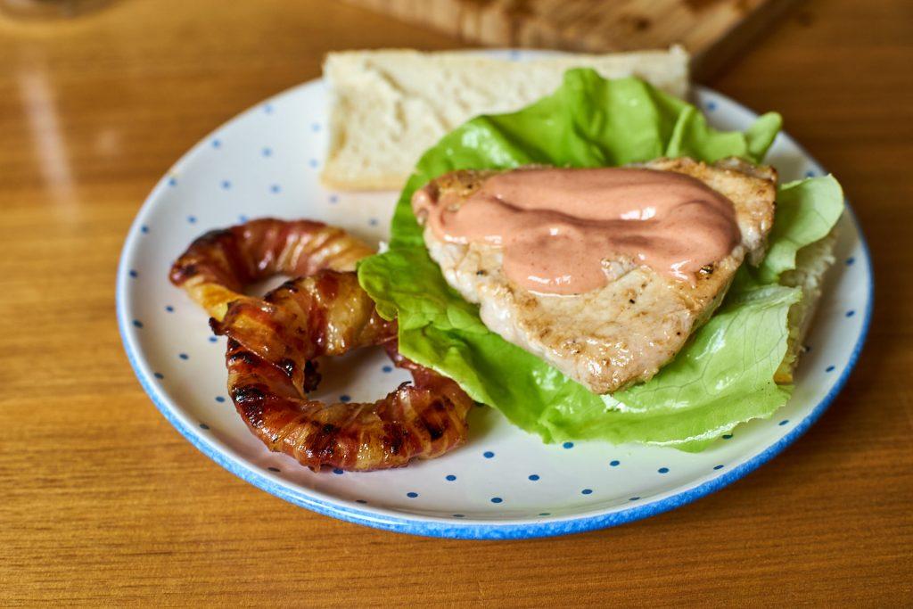 Mahlzeit! Kotelett-Burger mit Zwiebelringen angerichtet.