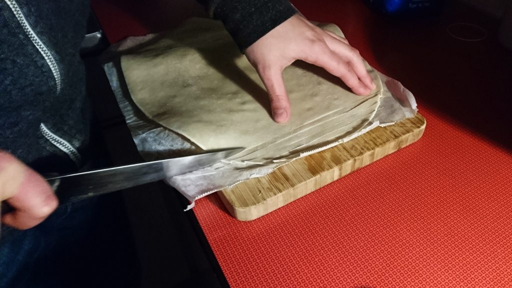 Der Teig für die Teigstangen wird geschnitten