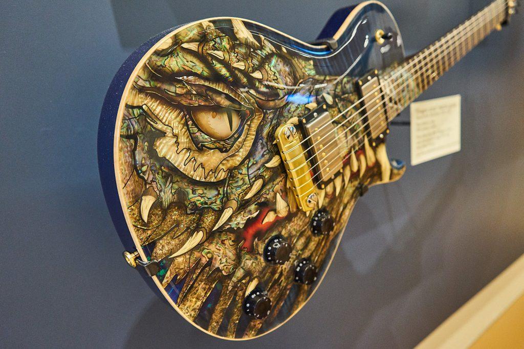 Eine Gitarre mit wunderschönen Perlmutteinlagen - in Form eines Drachen.