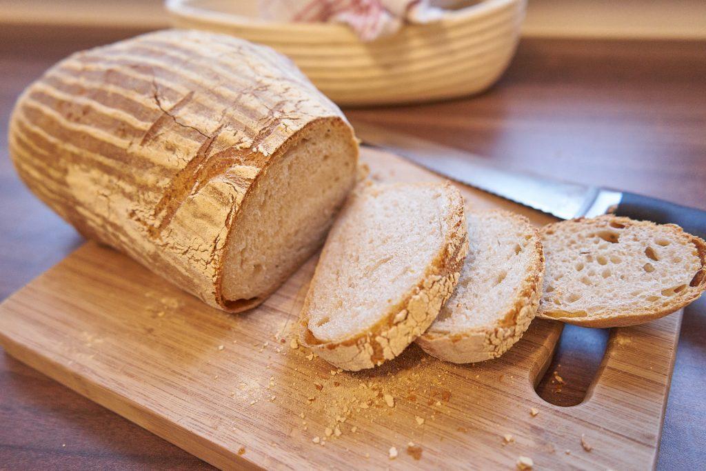 Ein Laib Brot mit ein paar herunter geschnittenen Scheiben.