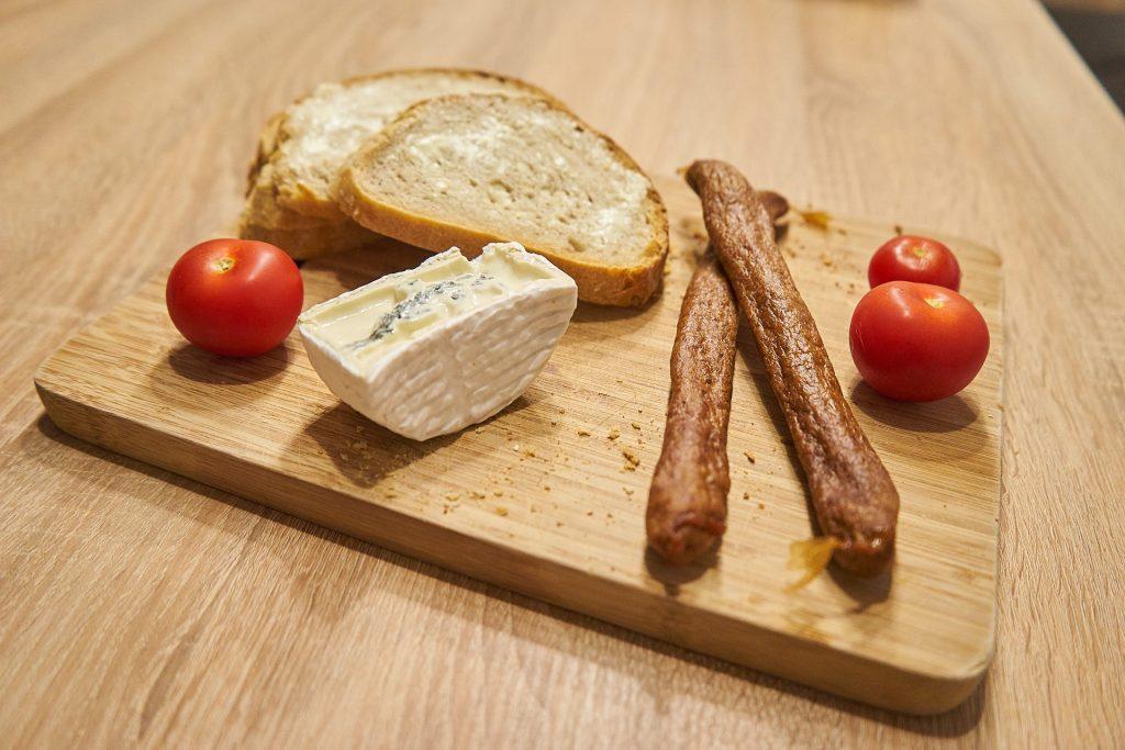 Brot mit Butter, Käse, Würsten und Tomaten.