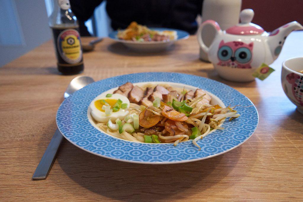 Eine Portion Ramen-Suppe mit Schweinebauch, Lauch, Gemüse und Ei.